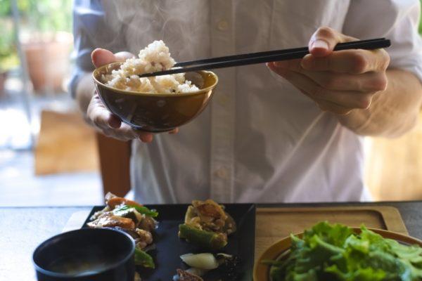 左利きでご飯を食べる男性